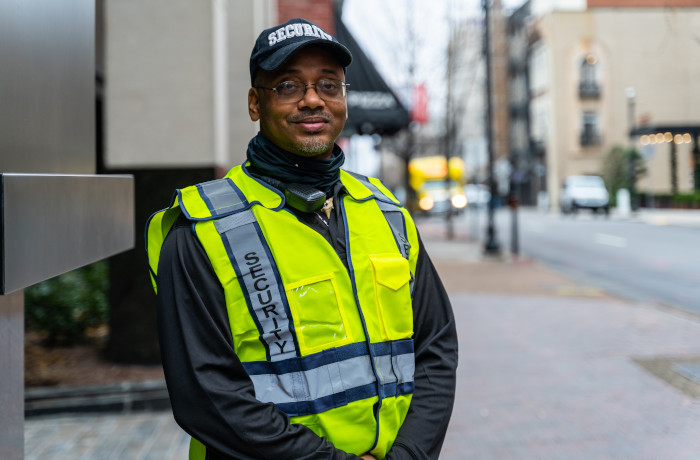A security guard wearing a reflective vest poses for a photograph