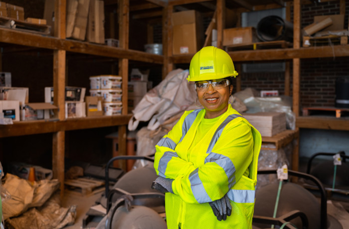 A woman in reflective vest and a hard hat posing in front of shelves