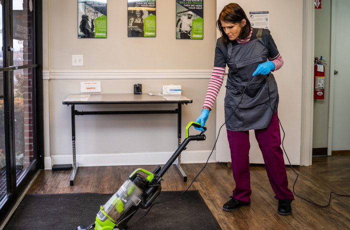 Janitorial staff using a vacuum to clean a rug near a door